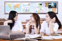 Drei Jugendstudenten, die in der Klasse plaudern Lizenzfreies Stockbild