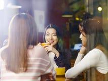 Drei junge asiatische Frauen, welche die Unterhaltung in der Kaffeestube plaudern lizenzfreie stockfotos