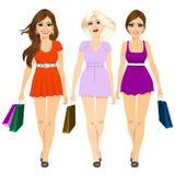 Drei junge attraktive lächelnde Mädchen in den Sommerminikleidern gehend und Einkaufstaschen halten Lizenzfreie Stockbilder
