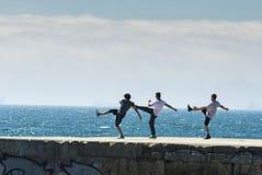 Drei Junge auf einem Wellenbrecher Stockfotos