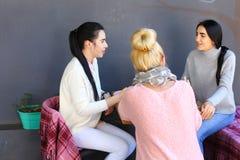 Drei junge ausgezeichnete Mädchenfreundinnen rattern und klatschen, sha Lizenzfreie Stockfotos