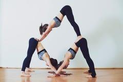 Drei junge Frauen, die acro Yoga im weißen Studio üben Lizenzfreie Stockfotos