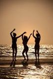 Drei junge Frauen, die auf Strand am Sonnenuntergang tanzen Lizenzfreie Stockfotografie