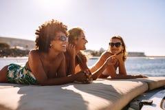Drei junge Frauen, die auf Yacht ein Sonnenbad nehmen lizenzfreies stockfoto