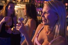 Drei junge Frauen, die an einem Nachtklub trinken Stockfotografie