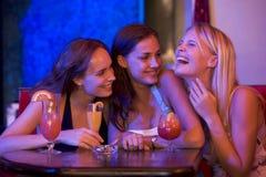 Drei junge Frauen, die an einem Tisch und an einem Lachen sitzen Lizenzfreies Stockfoto