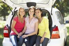 Drei junge Frauen, die im Stamm des Autos sitzen Stockbilder