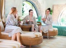Drei junge Frauen, die Tee am Kurort trinken stockbild