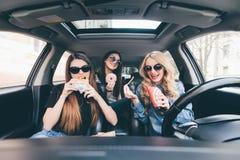 Drei junge Frauen fahren ein Auto, sprechen sich und essen einen Schnellimbiß in einem Auto im Stau Stockbild