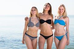 Drei junge Frauen im Bikini auf Strand stockfotografie