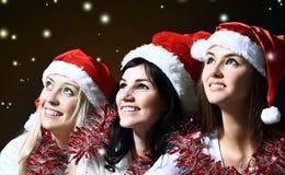 Drei junge Frauen im Kostüm von Santa Claus mit dem Einkaufen am Weihnachtshintergrund Lizenzfreie Stockfotos
