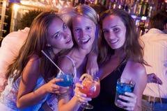 Drei junge Frauen mit Getränken in einem Nachtklub Stockfotografie