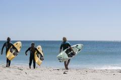 Drei junge Frauen tragen ihre Surfbretter. Stockfoto