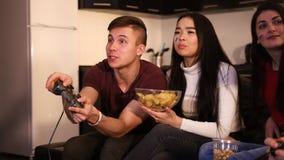Drei junge Freunde, die auf dem Sofa sitzen Junger Mann, der einen Steuerknüppel und Frauen Chips essend hält lizenzfreie stockfotos