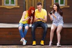 Drei junge Freunde, die aufpassendes Video auf Handy outd lachen stockfotografie