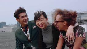 Drei junge Freunde, die in der Terrasse am Abend sitzen stock video footage
