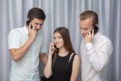 Drei junge Freunde, die draußen stehen und Handy betrachten stockfotos