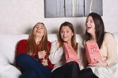 Drei junge Freunde, die Popcorn essen und Filme aufpassen Stockbild