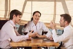 Drei junge Freunde, die Wein zusammen im Café essen Stockfotos