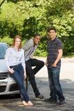 Drei junge Freunde mit einem Auto lizenzfreie stockfotografie