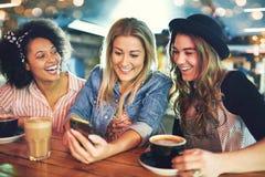 Drei junge Freundinnen, die über Kaffee sich entspannen Lizenzfreie Stockfotografie