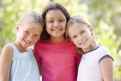 Drei junge Freundinnen, die draußen lächelnd stehen Stockbild