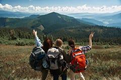 Drei junge Freundinnen erforschen grüne Berge lizenzfreie stockfotografie