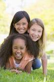 Drei junge Freundinnen oben angehäuft Stockbild
