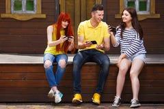Drei junge glückliche Freunde, die draußen bewegliches Videospiel spielen stockbild