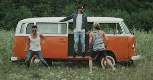 Drei junge Kerle, die vor einem Retro- Bus mitten in der Natur sehr charismatisch dacing sind stock video