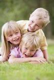 Drei junge Kinder, die draußen lächeln spielen Lizenzfreie Stockbilder