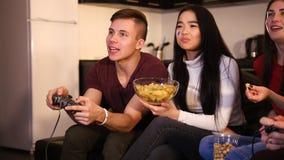 Drei junge Leute, die auf dem Sofa sitzen Junger Mann, der einen Steuerknüppel und Frauen Chips essend hält stockfotos