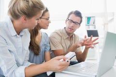 Drei junge Leute, die an Computer arbeiten Stockbild