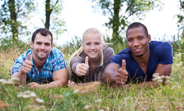 Drei junge Leute, die sich Daumen zeigen Stockfotografie
