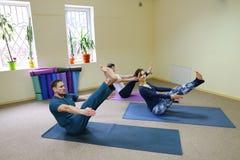 Drei junge Leute, die Yoga am Eignungsstudio tun stockbilder