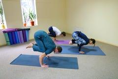Drei junge Leute, die Yoga am Eignungsstudio tun lizenzfreie stockfotos