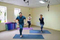 Drei junge Leute, die Yoga am Eignungsstudio tun lizenzfreie stockbilder