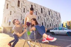 Drei junge Leute unterhalten auf Parkplatz mit Warenkorb lizenzfreie stockbilder