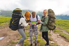 Drei junge Leute von Touristenfreunden: ein Kerl und zwei Mädchen blon stockbilder