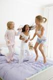 Drei junge Mädchen, die auf ein Bett springen Stockbild