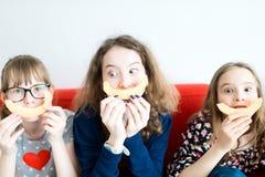 Drei junge Mädchen, die auf rotem Sofa sitzen und gelbe Melone essen lizenzfreie abbildung