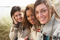 Drei junge Mädchen, die in den Sanddünen sitzen Stockbilder