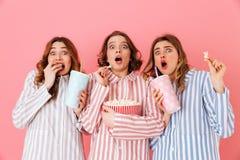 Drei junge Mädchen 20s, die buntes gestreiftes Pyjamas expressin tragen stockfoto