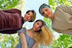 Drei junge Mädchen verbogen unten über die Erde im Himmel Lizenzfreie Stockbilder