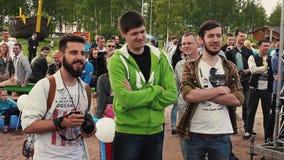 Drei junge Männer bleiben im Park unter anderen Besuchern Sommerfestival photograph stock video