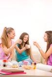 Drei junge Mädchen, die auf Sofa etwas trinken Stockbilder