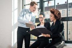 Drei junge nette Angestellte, die in einem modernen Büro lächeln Stockfoto