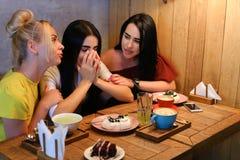 Drei junge nette Mädchenfreundinnen rattern und klatschen, Anteil secr Stockfoto