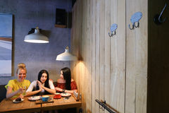 Drei junge nette Mädchenfreundinnen rattern und klatschen, Anteil secr Stockfotografie