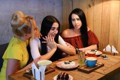 Drei junge nette Mädchenfreundinnen rattern und klatschen, Anteil secr Stockbild